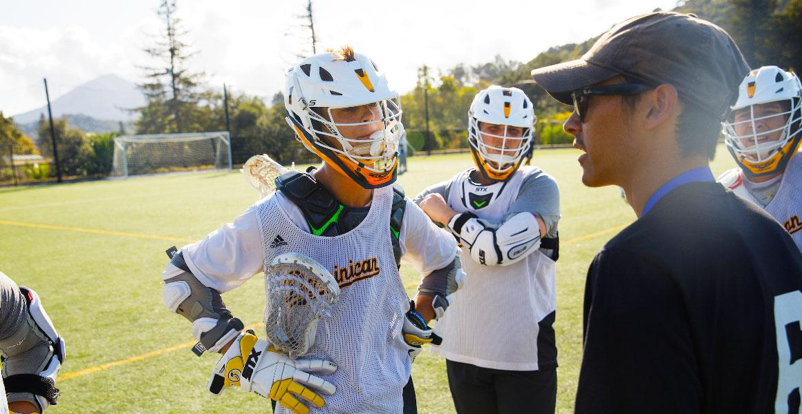 lacrosse players with coach