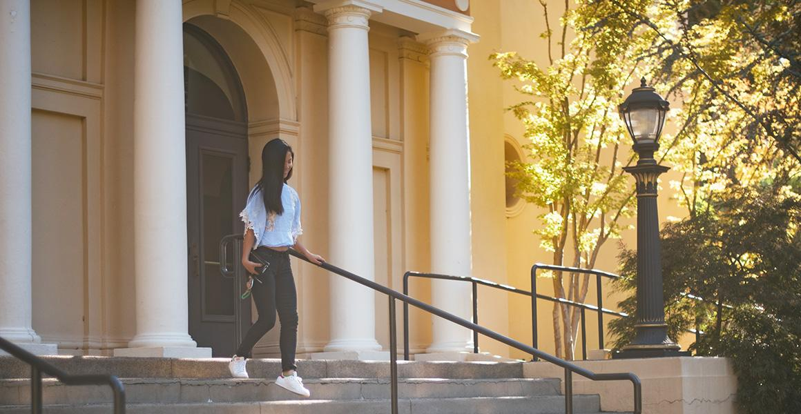 student walking down the steps of angelico hall