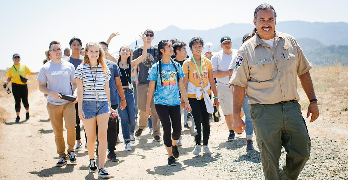 students hiking with park ranger