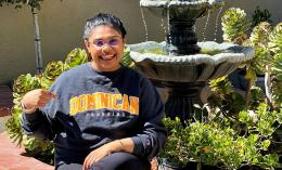 female student divya mistry wearing a Dominican sweatshirt sitting outside by a fountain.