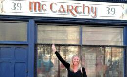 Karen McCarthy pointing at a Mc Carthy shop sign above her head
