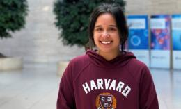 Photo of MS Graduate Melia Granath-Panelo wearing crimson Harvard sweatshirt in Buck Institute lobby