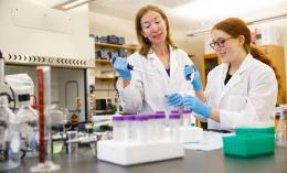Two women in white lab coats working in a lab