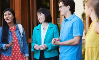 image of Dominican President Mary Marcy talking with students in front of Alemany Library