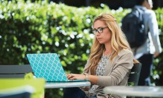 woman with eye glasses sitting outside at a table using a laptop