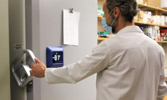 Photo of Professor Chris Endicott opening door of freezer in Science Building that will store COVID-19 vaccine