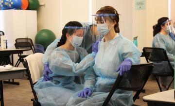 Occupational Therapy grad students doing lab work wearing PPE