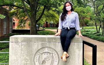 Dominican alumna Samantha Hunt wears a mask while sitting on concrete wall on Vanderbilt campus