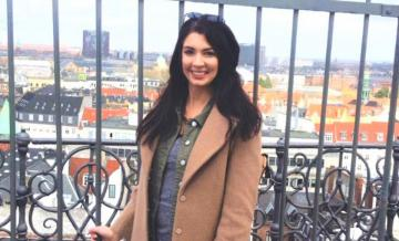 Cropped photo of MSBA student and ADC program grad Alison Wilcox standing in front of iron gate overlooking a city