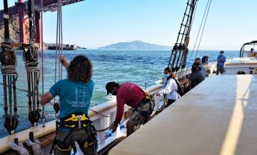 Image of students working on boat going under Golden Gate Bride as part of history class project