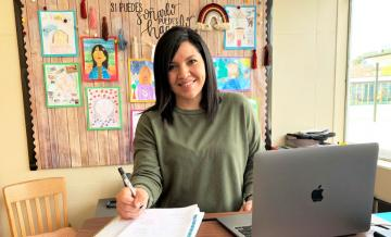 photo of Itta Gonzalez sitting at desk at Lynwood School for Teacher of Color Scholarship story
