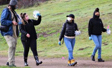 Photo of undergraduates walking with salamanders in plastic bags on path from research site in Point Reyes National Seashore