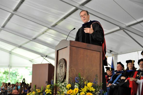 Photo of retired head of Student Life John Kennedy on stage at podium for 2013 Commencement