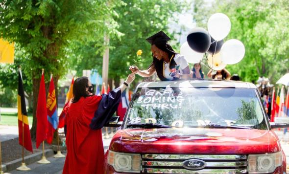 Photo of President Marcy handing yellow rose to graduate standing through sunroof at drive-thru celebration on campus