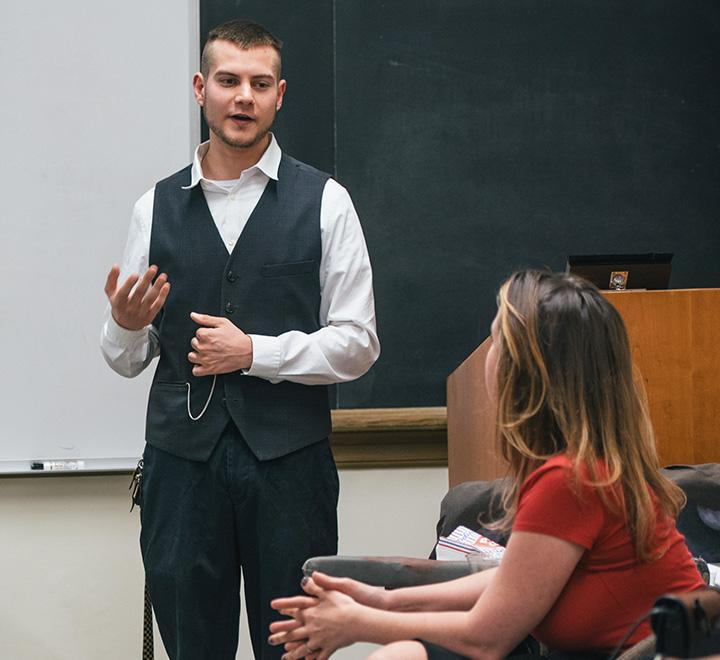student speaking from a podium in a classroom