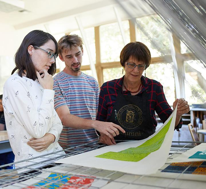students in art studio with faculty