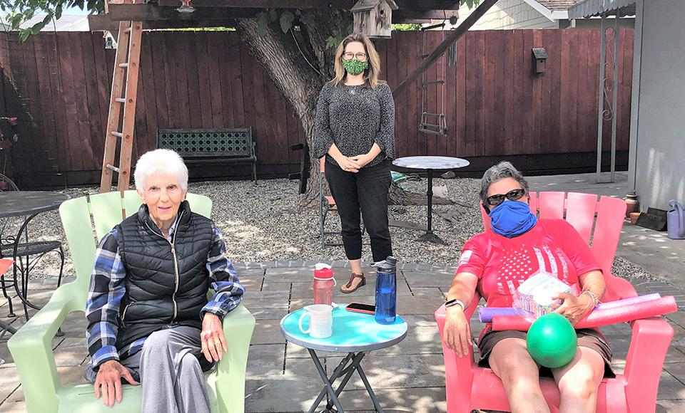 Three women sit and stand outside in a backyard during the Covid pandemic; two are wearing face masks.