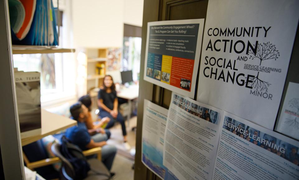 Community action and social change poster visible on a classroom door that is slightly open. Three students sit inside talking.